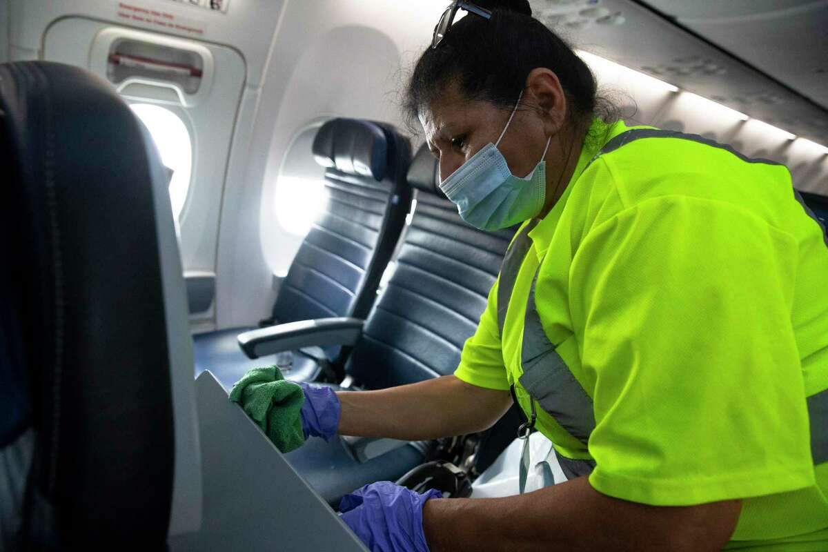 G2 Secure Staff member Angela Blanco cleans a tray tables on a United Airlines aircraft before the next flight Tuesday, July 7, 2020, at George Bush Intercontinental Airpo in Houston.
