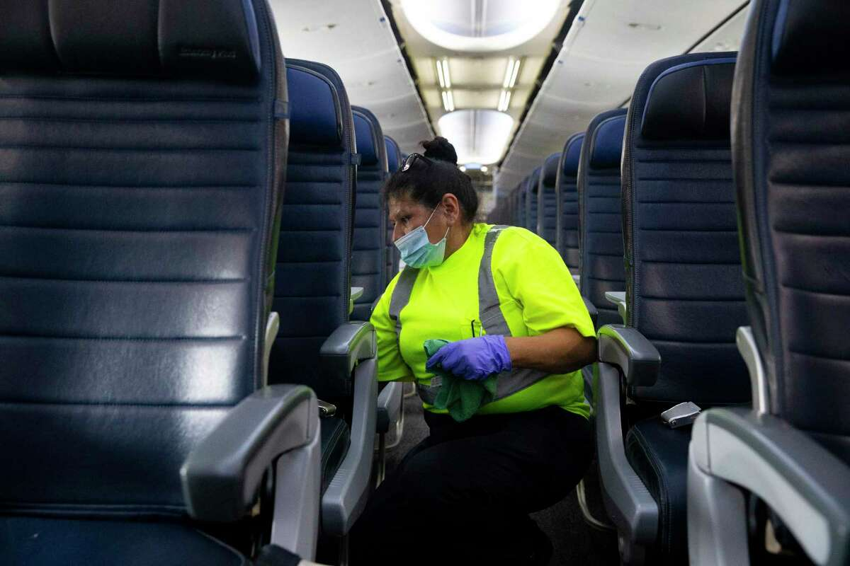 G2 Secure Staff member Angela Blanco vacuum cleaning a United Airlines aircraft before the next flight Tuesday, July 7, 2020, at George Bush Intercontinental Airpo in Houston.
