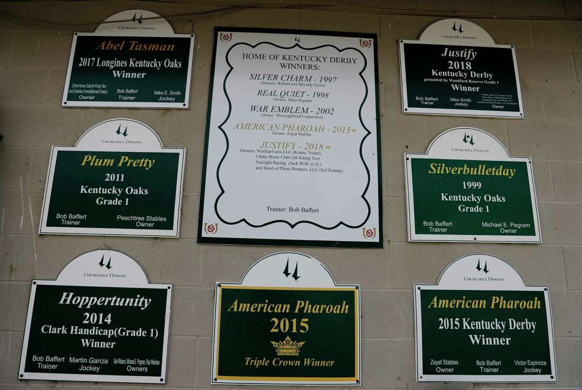 Plaques display the winning horses' names that have been trained by Bob Baffert on a training stable at Churchill Downs, Wednesday, April 22, 2020, in Louisville, Ky. (AP Photo/Darron Cummings)