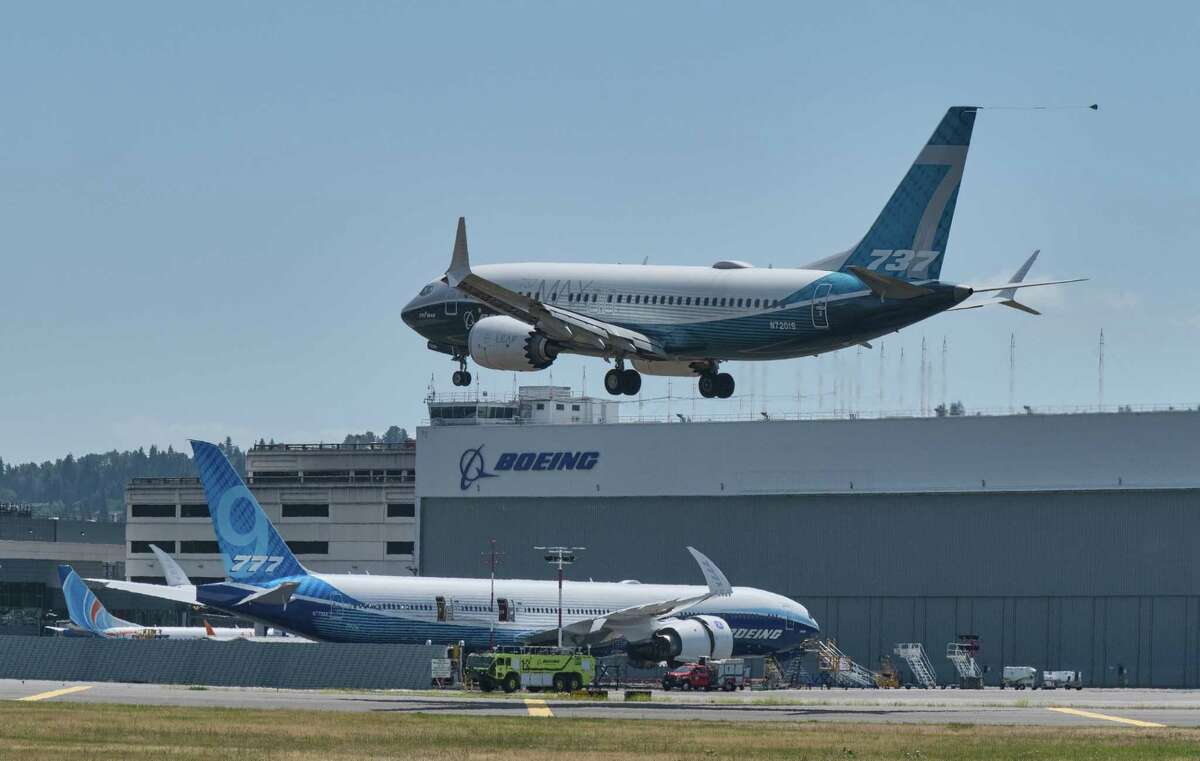 SEATTLE, WA - JUNE 29: A Boeing 737 MAX aircraft lands following a FAA recertification flight at Boeing Field on June 29, 2020 in Seattle, Washington. The 737 MAX has been grounded for commercial flights since March of 2019 following two crashes. In the background is a Boeing 777X test plane. (Photo by Stephen Brashear/Getty Images)