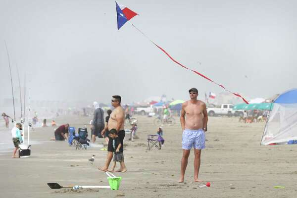 A beachgoer watches as a Texas theme kite flies over the beach in Port Aransas on Sunday. Vacationers claimed their spots, early setting up their shade tents in the morning and by early afternoon the beach was well packed. Many area hotels put out no vacancy signs as the popular vacation site is busy even during the pandemic.