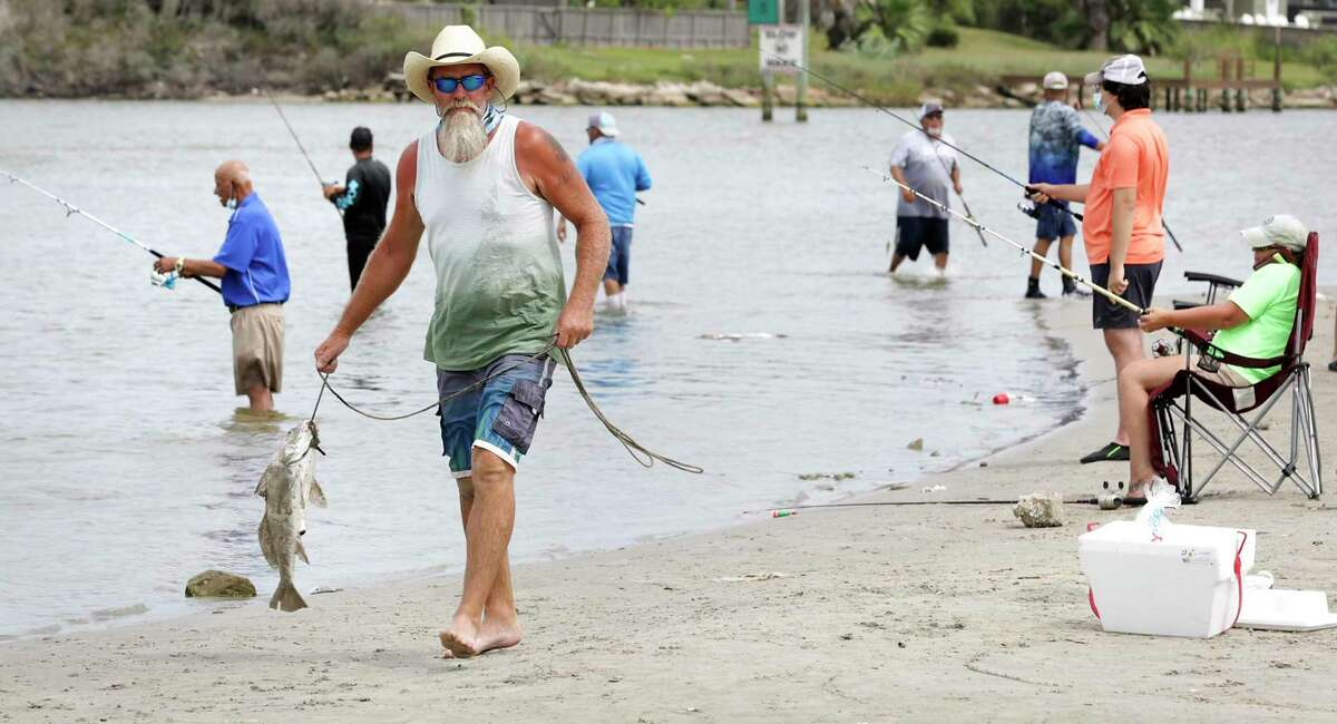 Bobby Campbell of Brady, Texas moves his catch, an almost 8 pound black drum, as fishermen pack the shores along the Packery Channel on Mustang Island south of Port Aransas.