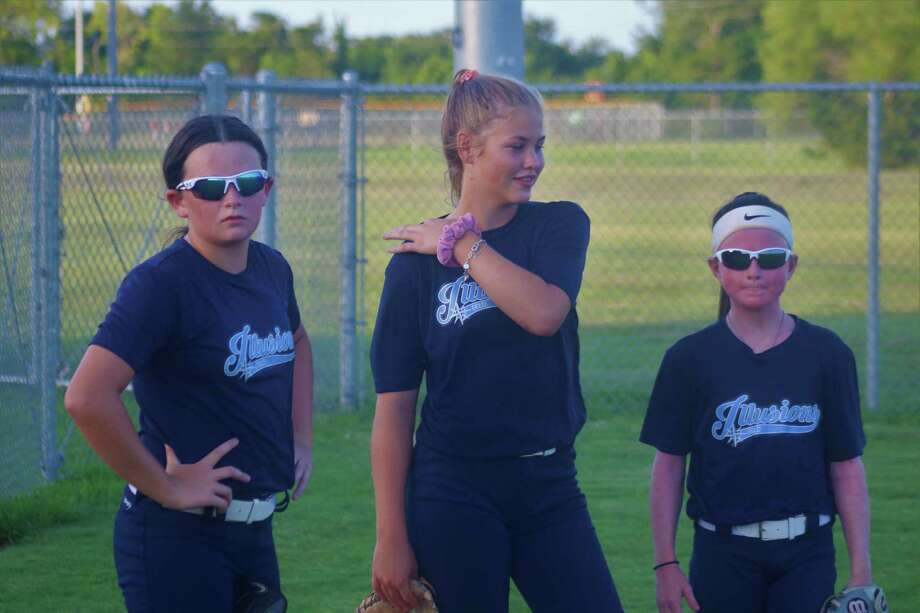 From L-R, Mylee McRae, Ella Mangus and Hannah Baimbridge wait for their respective turns to shag fly balls in the outfield at the Deer Park Softball Complex Monday night. Photo: Robert Avery