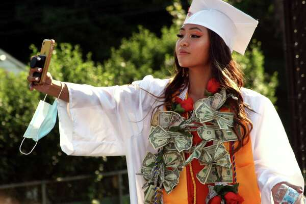 Graduate Annaly Khanthaphixay takes a selfie as she wear a traditional Laos money lei before the start of the Class of 2020's 144th Commencement Ceremony at Ryan Field in Derby, Conn., on Wednesday July 15, 2020.