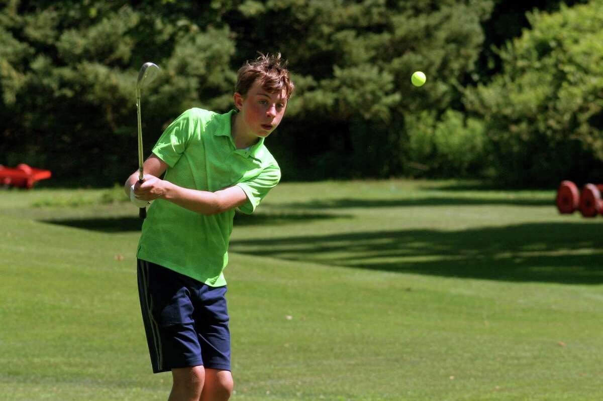 Resident Cameron Raney, 13, practices chipping after nine holes of golf at The Carl Dickman Par 3 Golf Course in Fairfield, Conn., on Tuesday July 14, 2020.