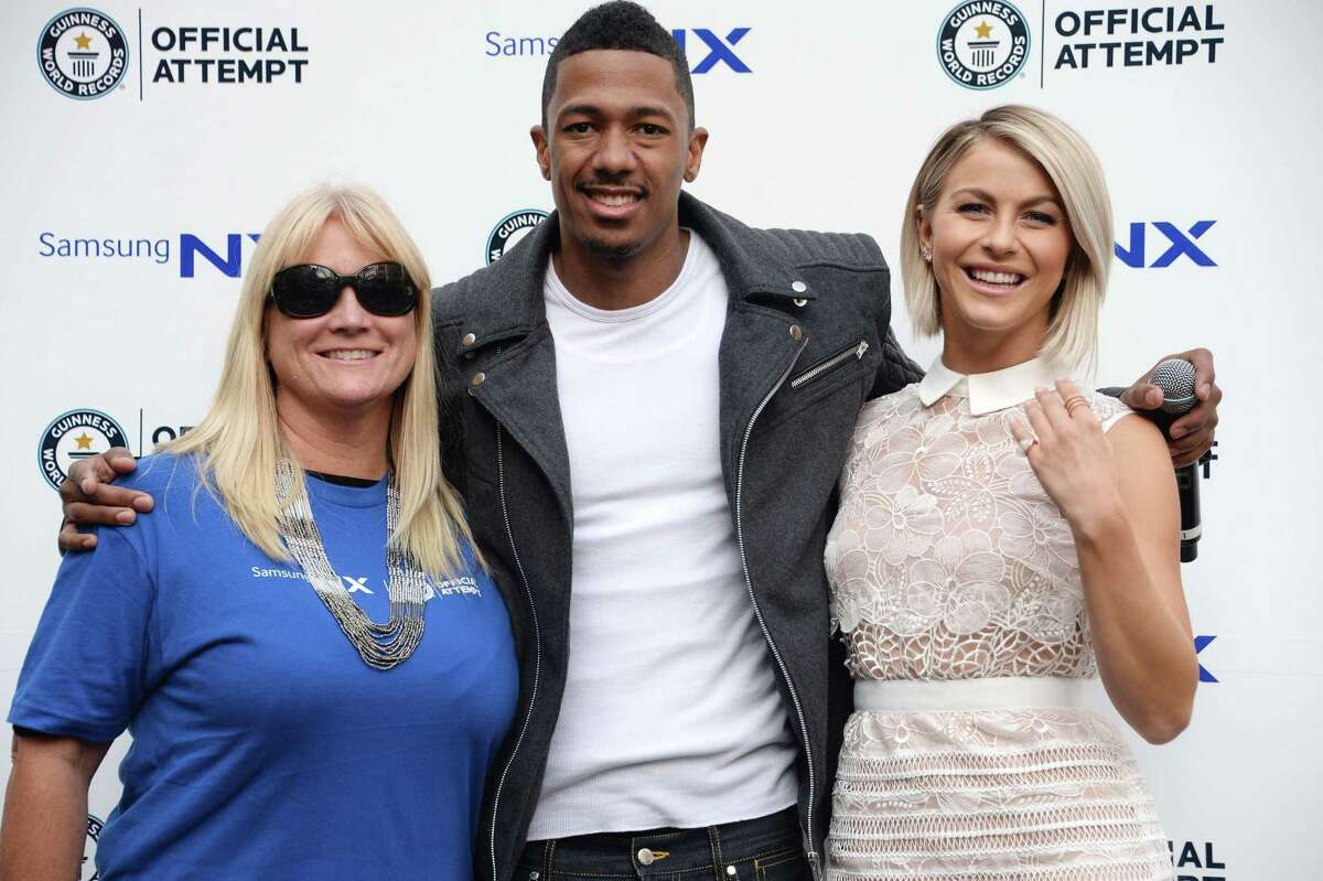 Actors Nick Cannon (C) and Julianne Hough (R) pose with Erin Rank (L), President & CEO Habitat for Humanity of Greater Los Angeles before and attempt to break the Guinness World Record for the longest selfie relay chain, October 14, 2014 at the Hollywood and Highland complex in Hollywood, California. Organized by Samsung to promote their new cameras and benefiting Habitat for Humanity of Greater Los Angeles, 288 participants created the longest selfie relay chain to successfully break the Guinness World Record set in May in Sydney, Australia with 279 participants. Samsung will donate $50,000 to Habitat for Humanity of Greater Los Angeles to mark the new world record. AFP PHOTO / Robyn BeckROBYN BECK/AFP/Getty Images ORG XMIT: US-GUINNE