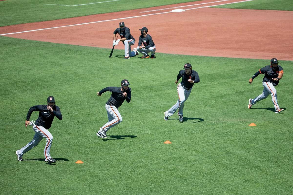 San Francisco Giants players run drills during the San Francisco Giants' summer training camp session at Oracle Park in San Francisco, Calif. Saturday, July 4, 2020. Due to COVID-19, the 2020 MLB season has been postponed with players just beginning to return for warmups and practices while wearing masks and keeping social distance.