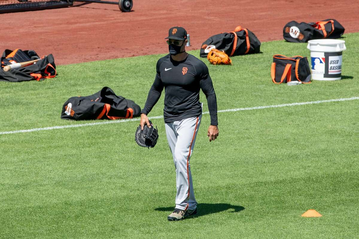 San Francisco Giants manager Gabe Kapler wears a mask while walking on the field during the San Francisco Giants' summer training camp session at Oracle Park in San Francisco, Calif. Saturday, July 4, 2020. Due to COVID-19, the 2020 MLB season has been postponed with players just beginning to return for warmups and practices while wearing masks and keeping social distance.