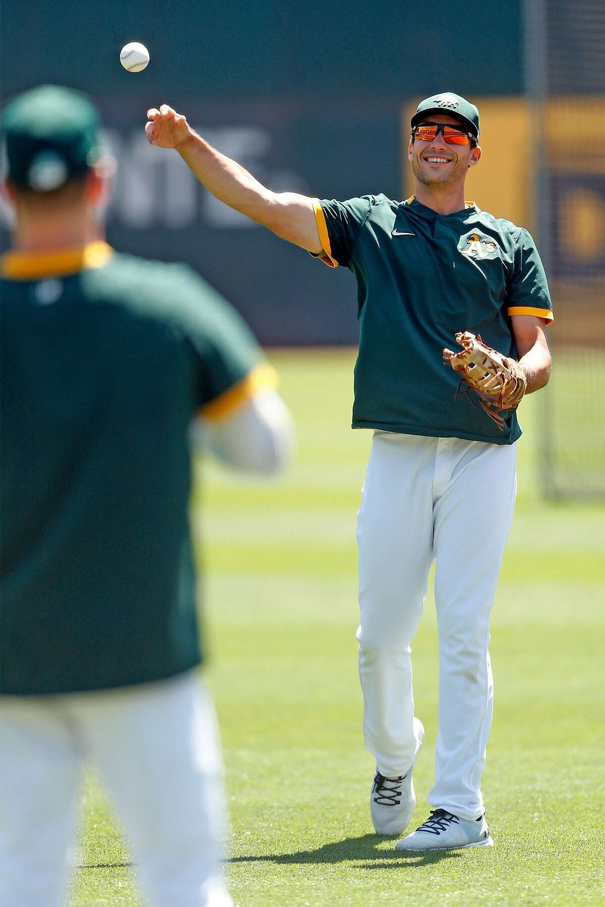 Oakland Athletics' Matt Olson tosses a baseball to Matt Chapman during practice at Oakland Coliseum in Oakland, Calif., on Wednesday, July 8, 2020.