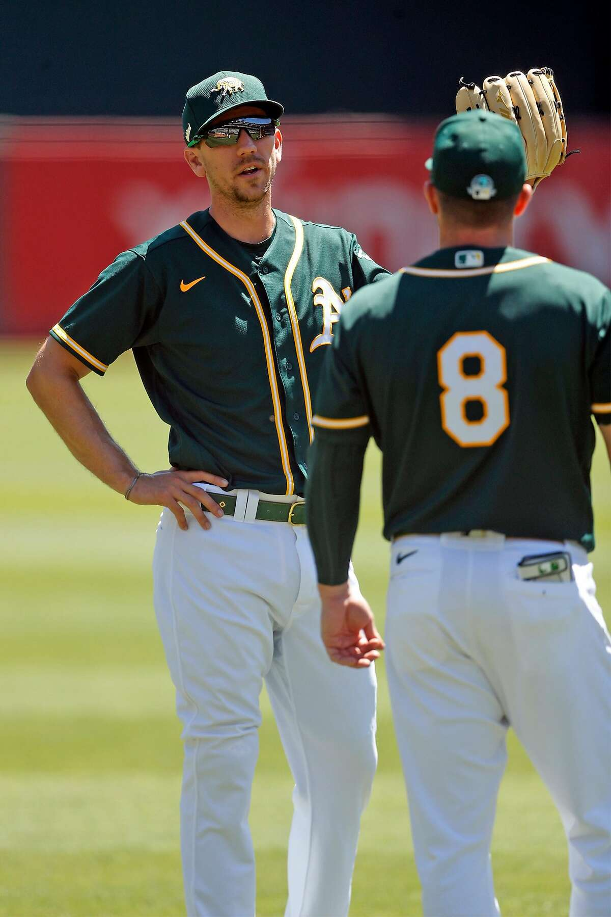 Oakland Athletics' Stephen Piscotty talks with Robbie Grossman (8) before simulated game at Oakland Coliseum in Oakland, Calif., on Sunday, July 12, 2020.