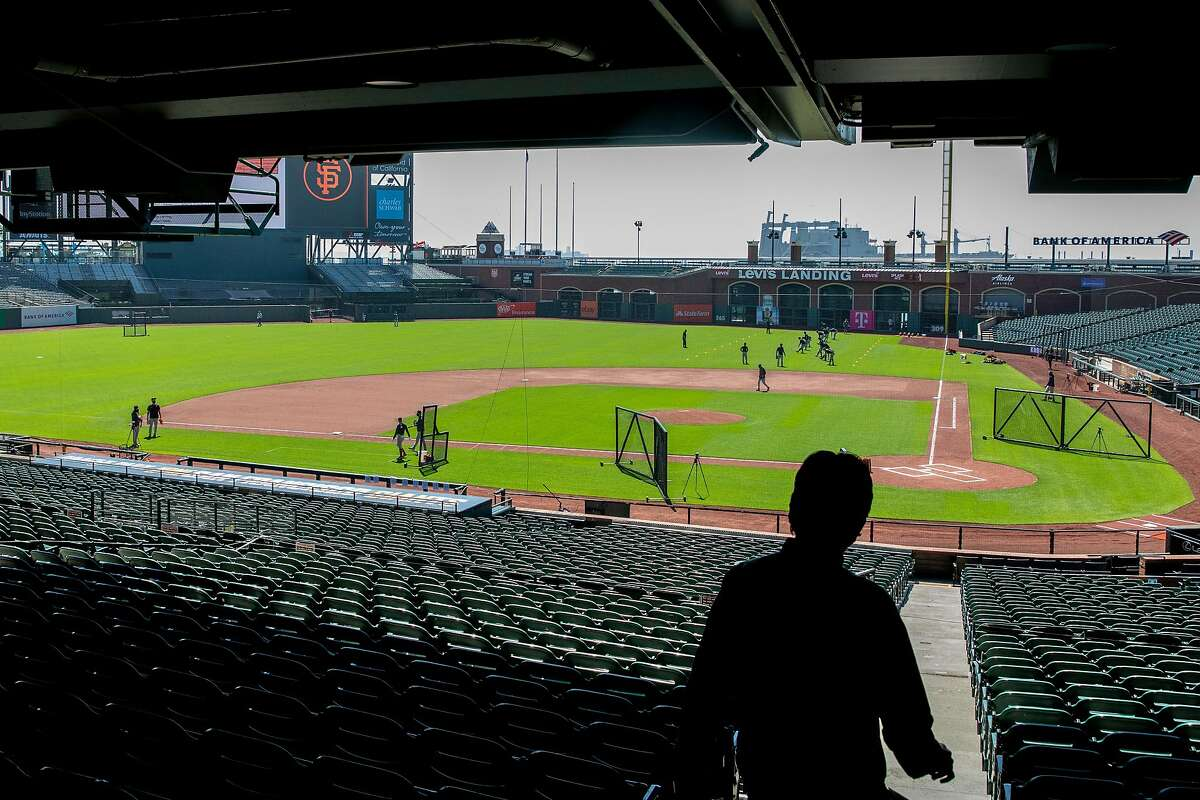 Players take to the field during the San Francisco Giants' summer training camp session at Oracle Park in San Francisco, Calif. Saturday, July 4, 2020. Due to COVID-19, the 2020 MLB season has been postponed with players just beginning to return for warmups and practices while wearing masks and keeping social distance.
