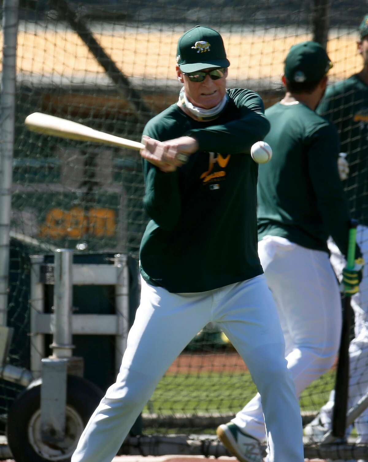 Manager Bob Melvin hits grounders to infielders during the Oakland A's summer training camp at the Coliseum in Oakland, Calif. on Saturday, July 11, 2020.