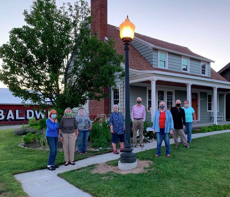 Lake County Historical Society Museum and Library members gathered for the first lighting of a donated 1920s vintage light pole installed on the museum grounds July 13. The light will be lit each evening at dusk. ( Submitted photo)