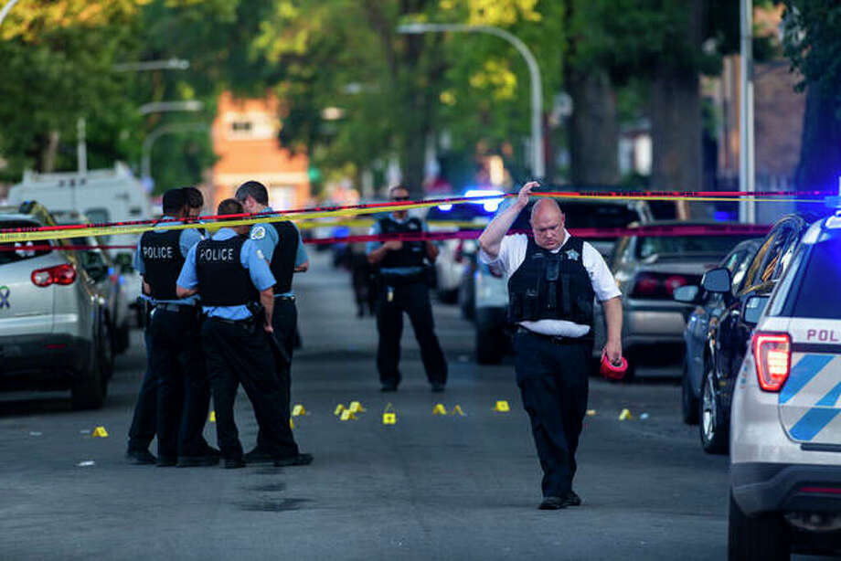 Chicago police officers investigate the scene of a deadly shooting July 5 in Chicago, where a 7-year-old girl and a man were fatally shot during a Fourth of July party. Photo: Tyler LaRiviere | Chicago Sun-Times Via AP