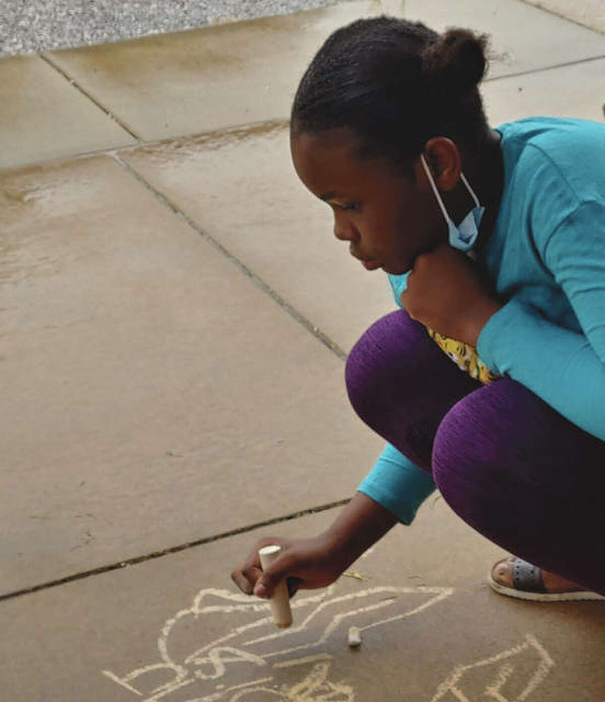 Rayne Esengo, 11, the daughter of Sandra Muke, draws with chalk Wednesday at the VAS Housing units during Midwest Youth Services' Round Table Summer Lunch program.