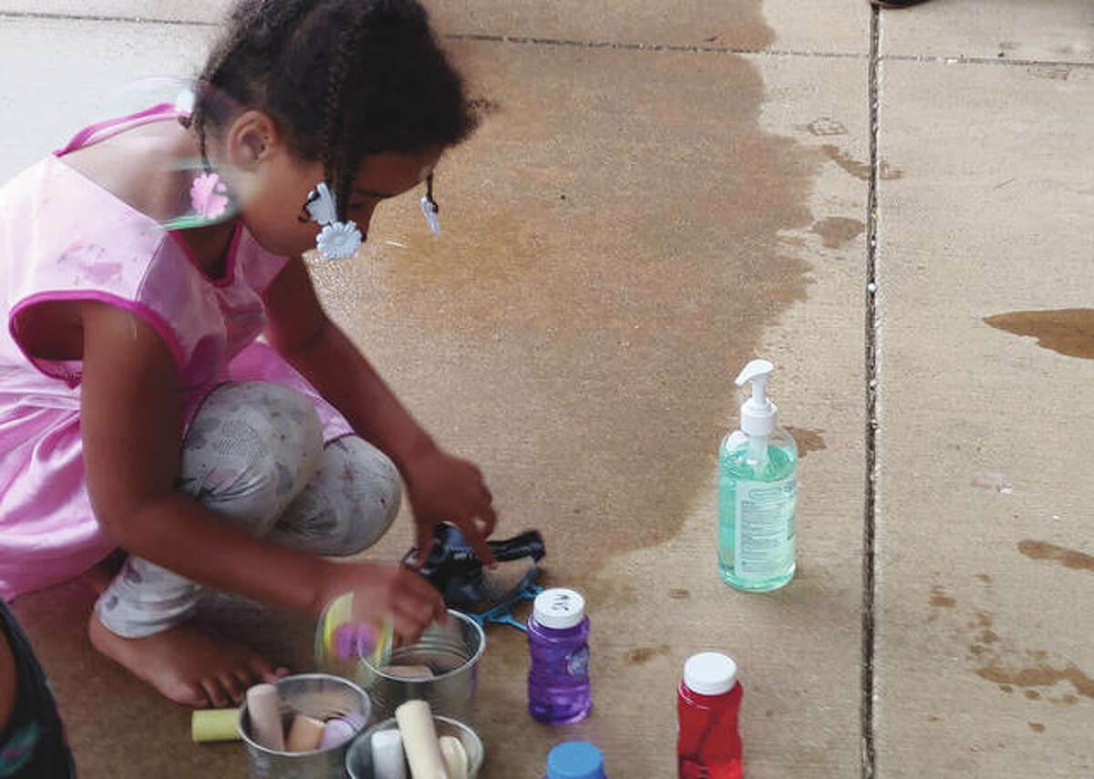 Naveah White, 5, the daughter of Christie Mehroff of Jacksonville, draws with chalk Wednesday at the VAS Housing units during Midwest Youth Services' Round Table Summer Lunch program.