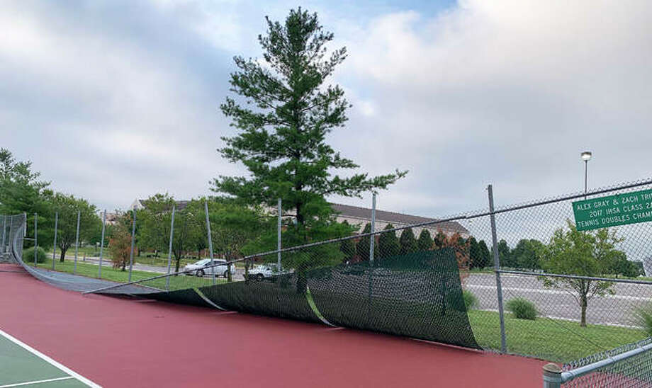 The Edwardsville High School tennis facility sustained damage during Wednesday's thunderstorm that produced wind speeds up to 75 miles per hour and heavy rain. A fence on the front of the facility that stretched between the two pavilions was damaged. Despite the damage, a handful of Edwardsville area residents were out early Thursday morning playing. Photo: Matt Kamp|The Intelligencer