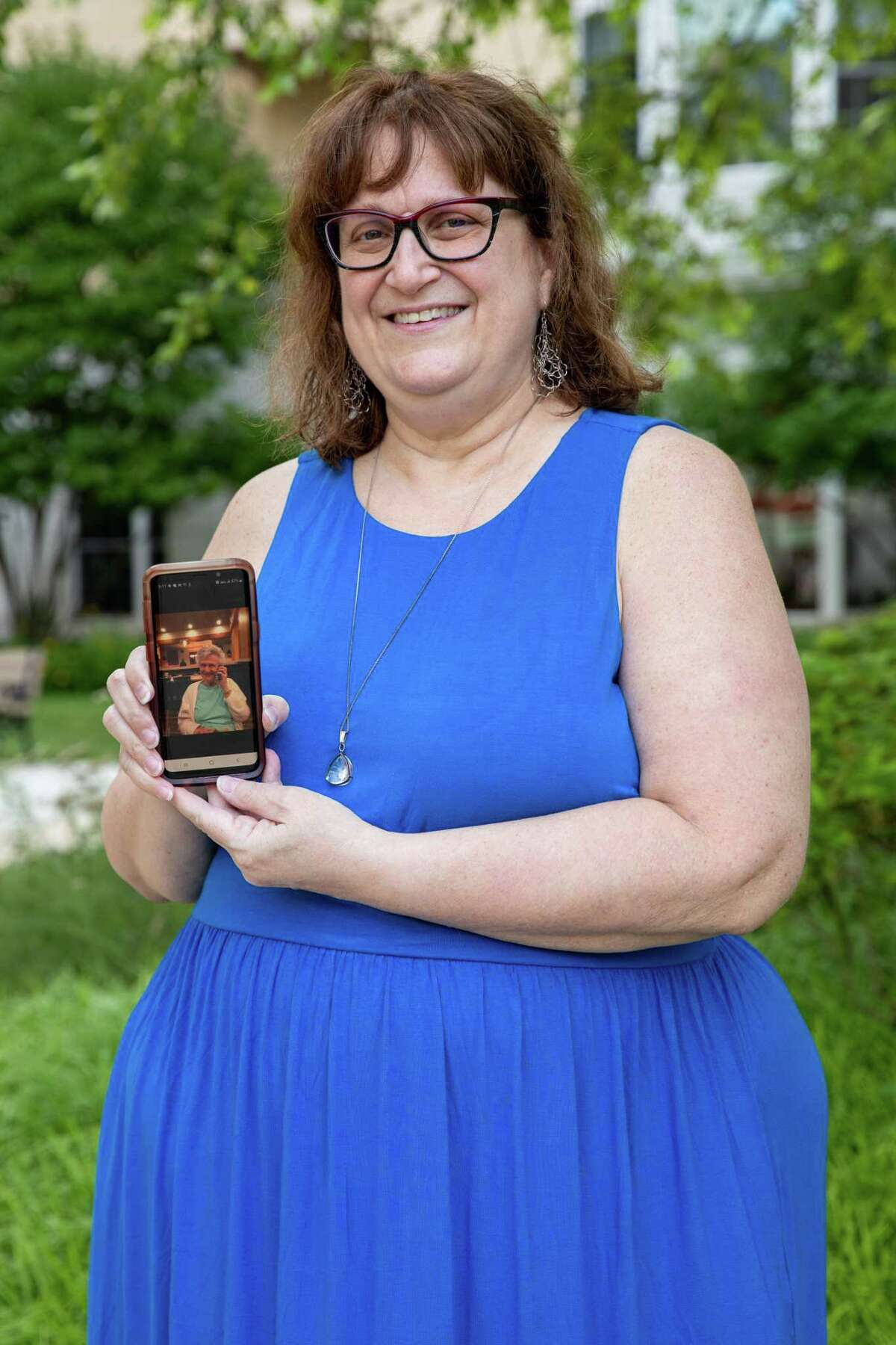 Michele Rubinstein holds up a photo of her mother Helen Rubinstein who lives in Ingleside at King Farm in Rockville, Md.