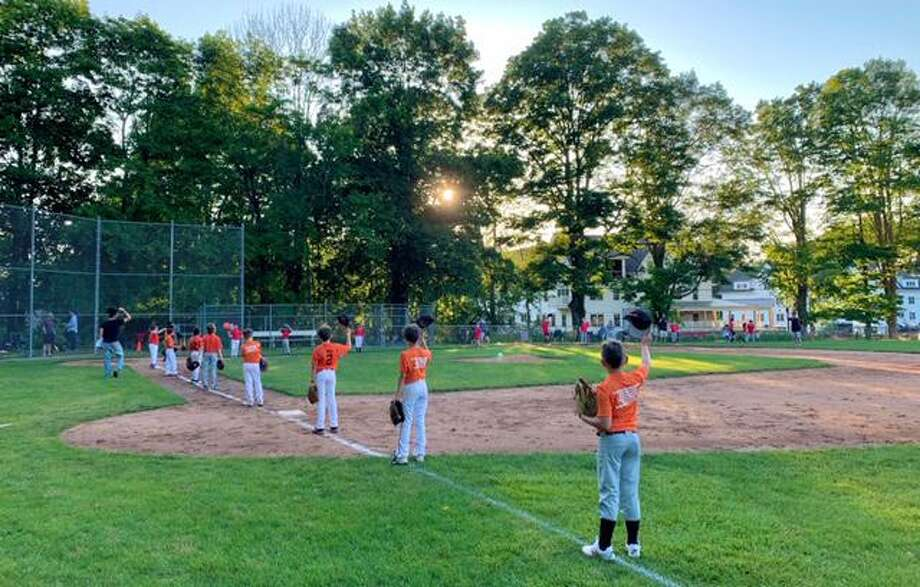 Players raise their caps to salute one another before a recent Ridgefield Little League game. Photo: Contributed Photo / Ridgefield Little League