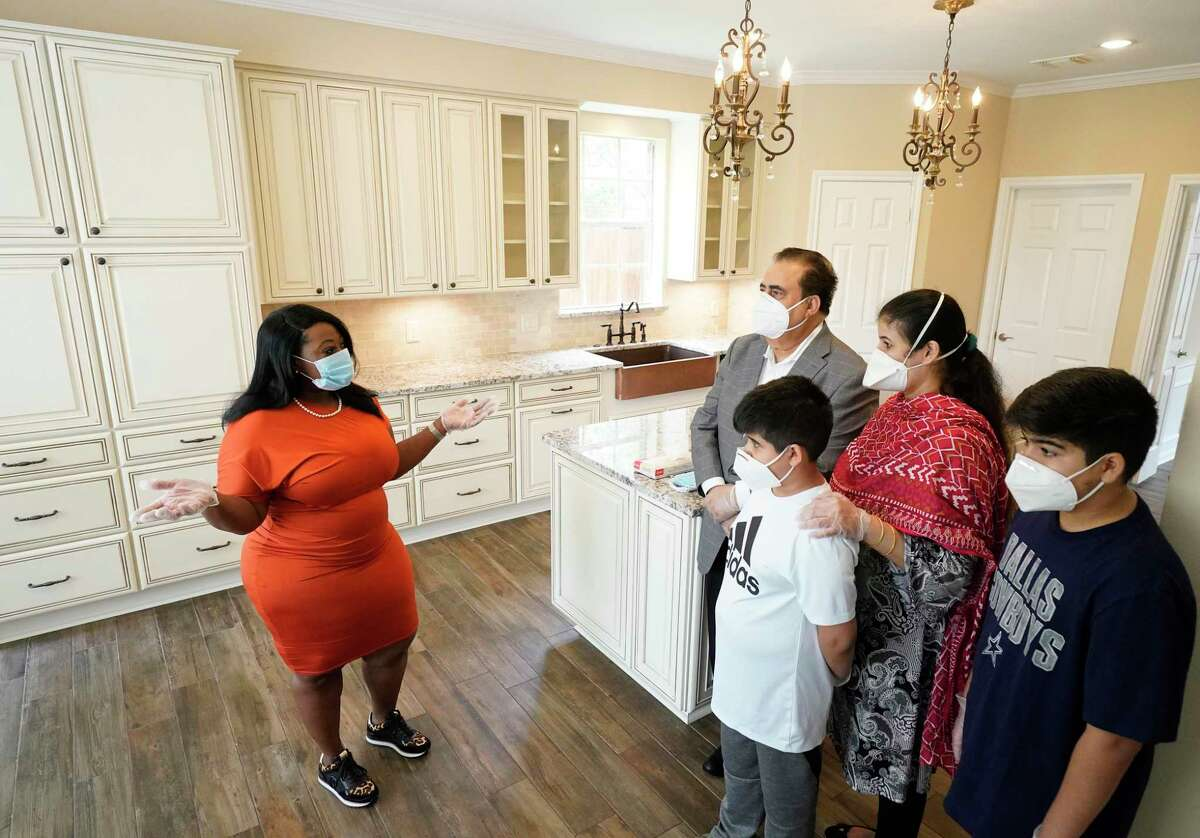 Tiffany Curry of Berkshire Hathaway HomeServices Tiffany Curry & Co., left,, talks with Shabir Brohi and his wife, Bano Brohi, and their sons, Shaan Brohi, 8, and Fazal Brohi, 11, right, at an open house Saturday, June 27, 2020, in Sugar Land.