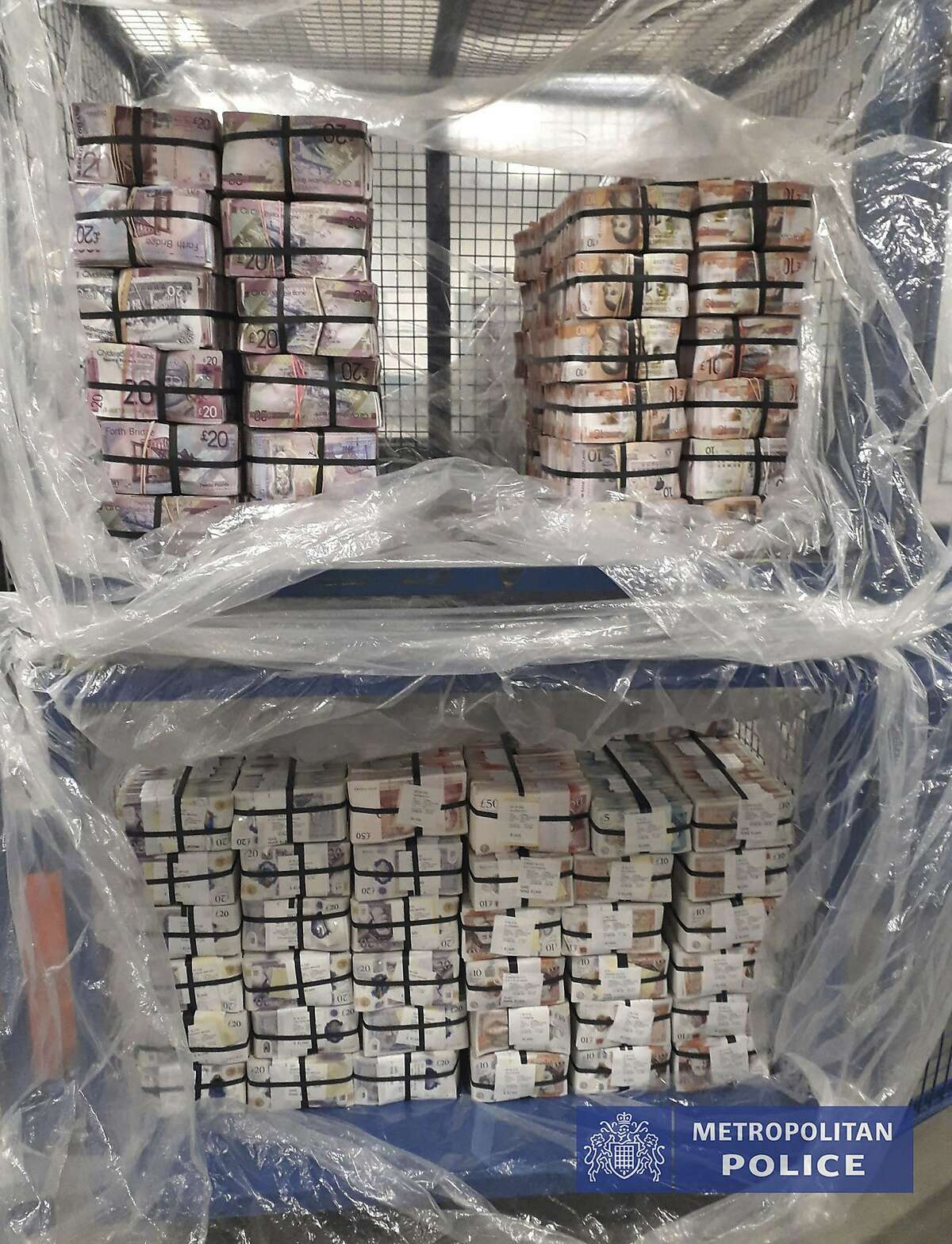 In this photo issued Thursday July 2, 2020, by the London Metropolitan Police showing cash worth 5.1 million pounds, seized in Operation Venetic, an investigation on Encrochat, a military-grade encrypted communication system used by organised criminals trading in drugs and guns. According to information released by police authorities, officers in the UK had arrested 307 suspects, recovered 106 Encrochat devices and seized many millions in currency, with many thousands of officers involved in a massive international sting. (Metropolitan Police via AP)