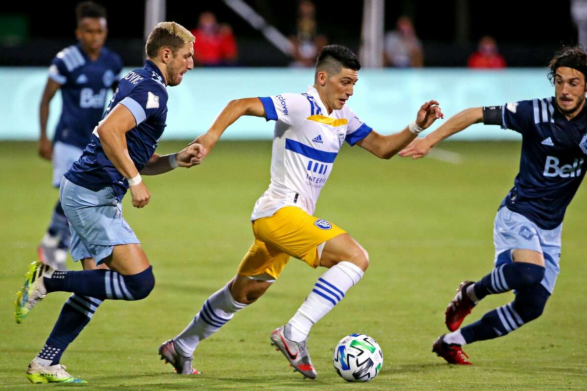 San Jose Earthquakes forward Cristian Espinoza (10) controls the ball against Vancouver Whitecaps midfielder David Milinkovic (7) during the first half at ESPN Wide World of Sports on July 15, 2020 in Orlando, FL.