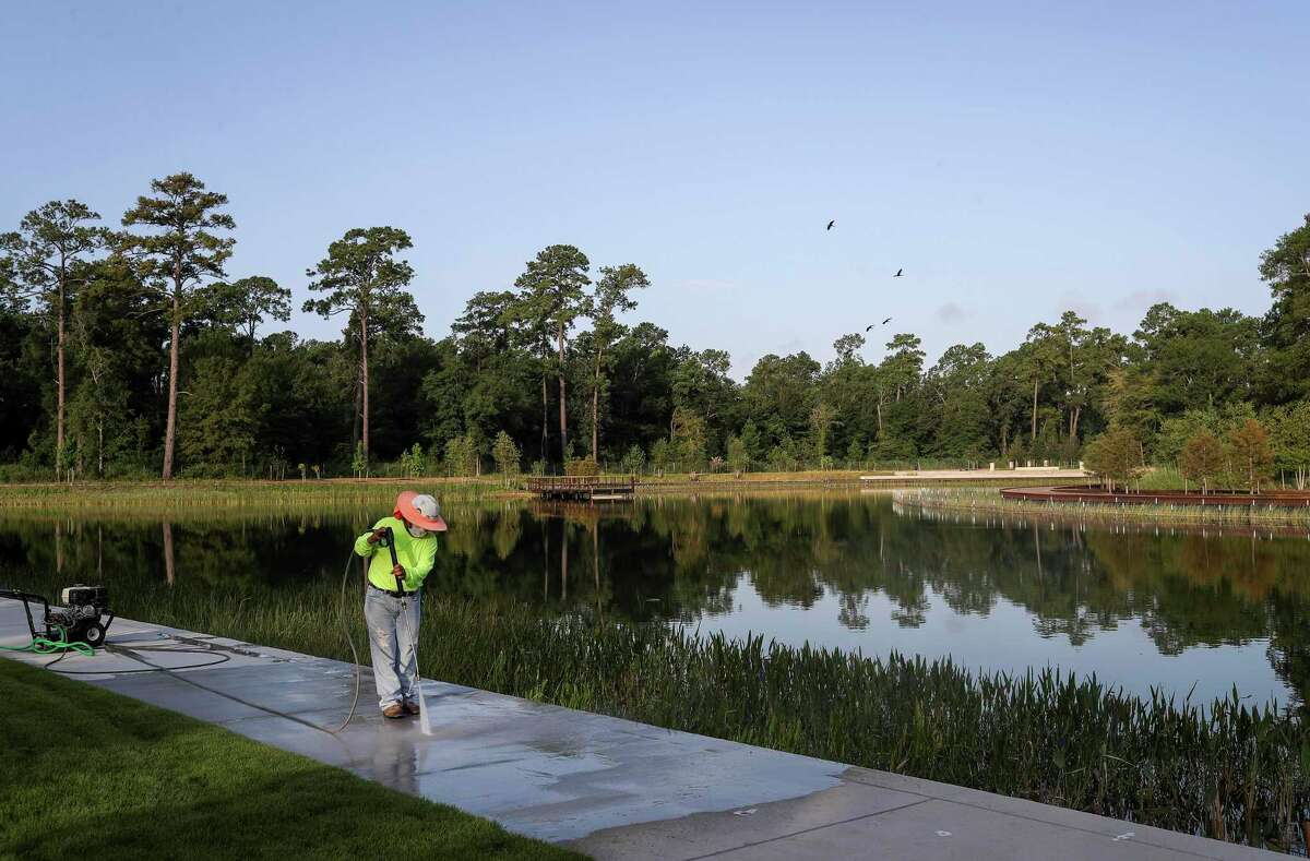 Rosario Perez cleans the sidewalk around Hines Lake on Wednesday, July 15, 2020, in the Clay Family Eastern Glades section of Memorial Park in Houston. The 100-acre section is scheduled to open to the public at the end of the month.
