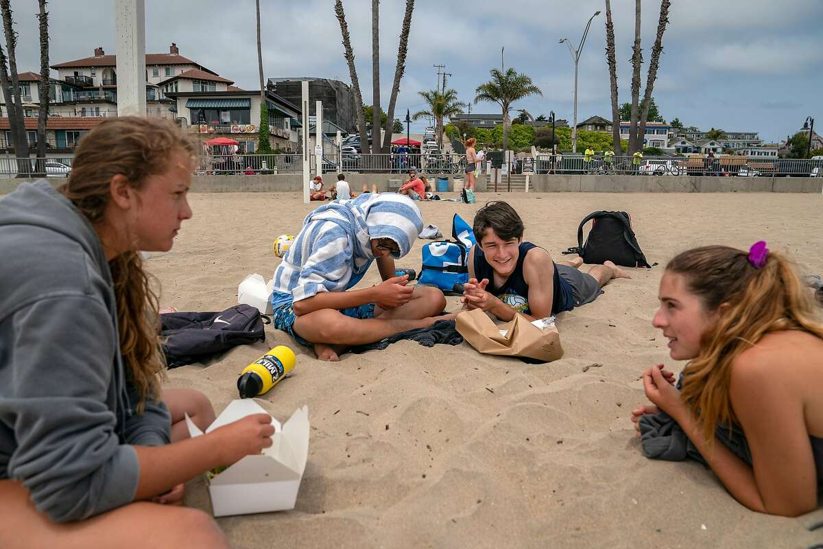 From left, Santa Cruz High School students, Alex Hariri, 16, Leo Tuncer, 16, Ben Pearson, 15, and Marilu Pally, 16, relax near the volleyball courts on Santa Cruz Beach on Wednesday, July 15, 2020 in Santa Cruz, Calif.