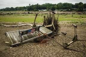 Debris is strewn about the lakebed of Sanford Lake Thursday, July 16, 2020 near N. Water Road. (Katy Kildee/kkildee@mdn.net)