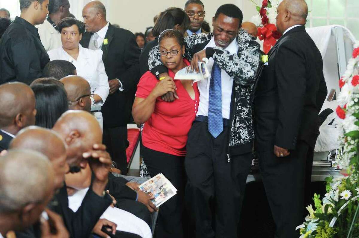Family and friends attend the funeral for Amos