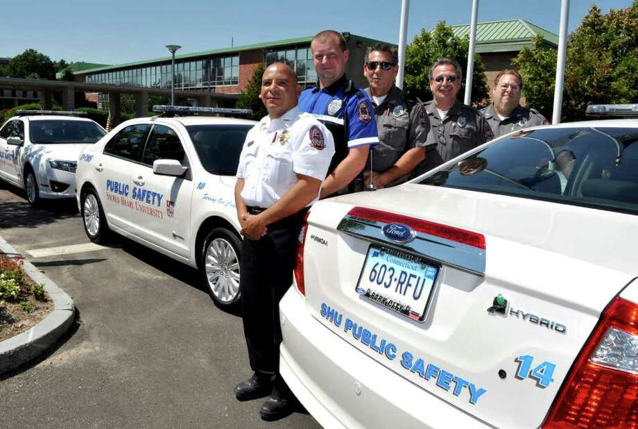 Sacred Heart University's Department of Public Safety recently purchased four hybrid vehicles to use on patrols. With the Ford Fusion cruisers are, from left, SHU Public Safety Director Jack Fernandez and Public Safety Officers Dave Stevens, Bing Benson, John Kichinko and Scott Lupo. Photo: Contributed Photo / Fairfield Citizen