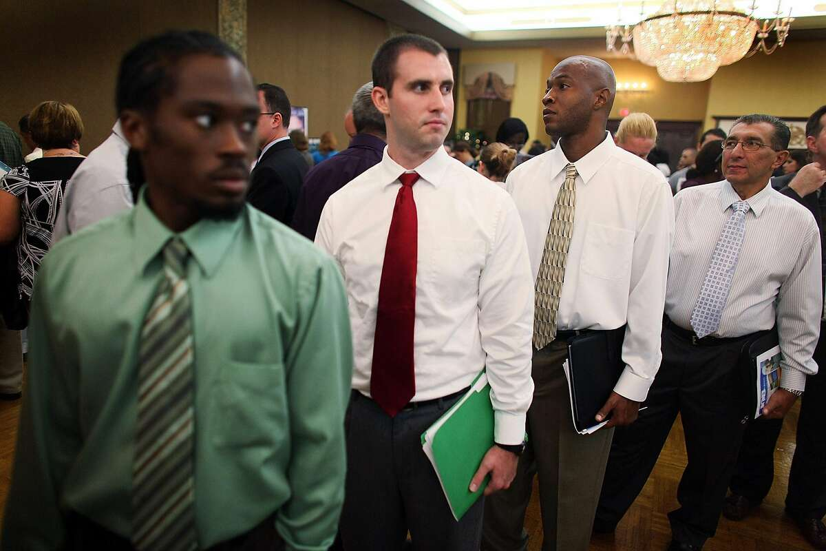 DAVIE, FL - SEPTEMBER 24: Rashad Ingraham (L-R) William Haselberger, Dietrick Purvis and Carlos Estevez, all unemployed, look for a job at the Diversity Job Fair on September 24, 2009 in Davie, Florida. Employers were hiring for positions in all types of industries such as law enforcement, waste management, insurance. (Photo by Joe Raedle/Getty Images)
