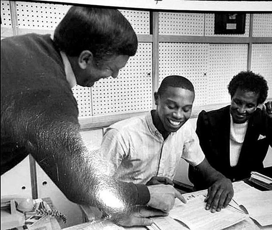 From left, former Alton basketball coach the late Stan McAfoos, Larry Smith and Smith's mother, Felicia Caldwell, at Smith's U of I college signing day in the old Alton High cafeteria in 1986. Photo: Telegraph File Photo
