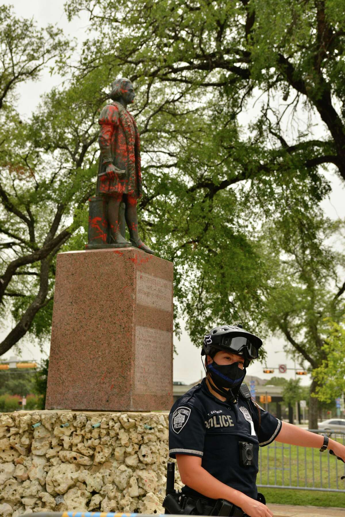 Police stand guard around the Christopher Columbus statue after a demonstration in the park Saturday afternoon.