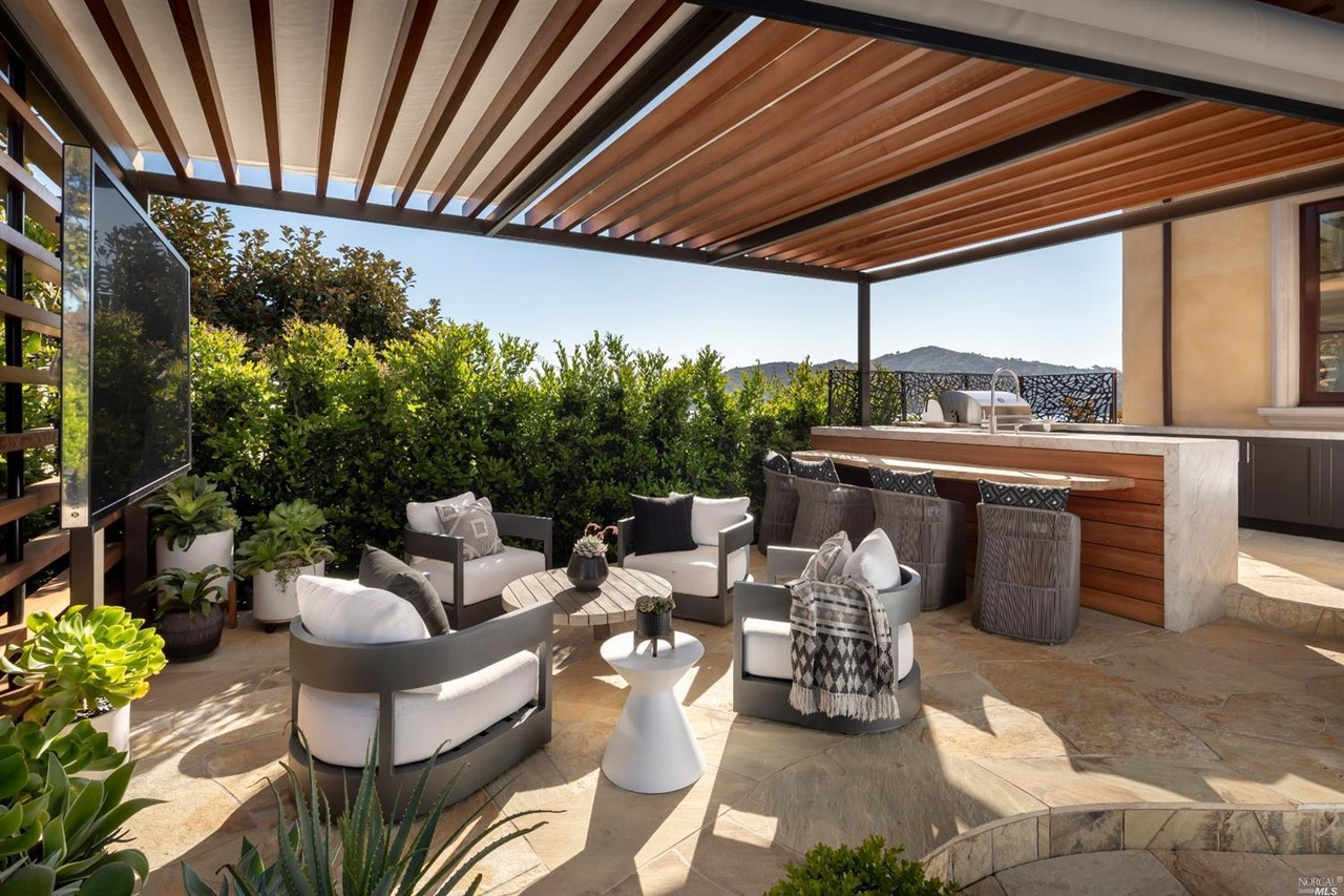 One of the more secluded patios towards the front of the property has an outdoor kitchen and seating area with a pergola and a flat-screen TV.