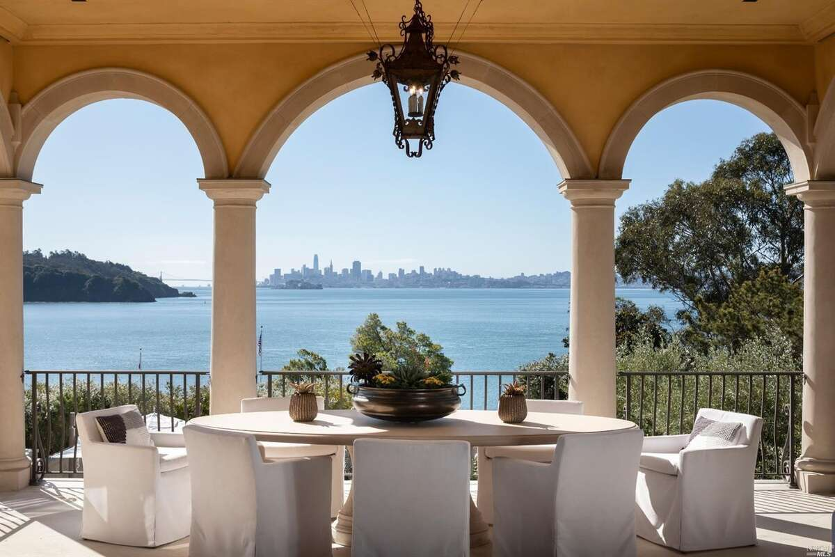The interior entertaining spaces lead out to a covered outdoor dining area with stunning bay and city views.