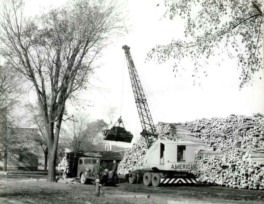 A crane moves logs at American Boxboard, circa 1950s.