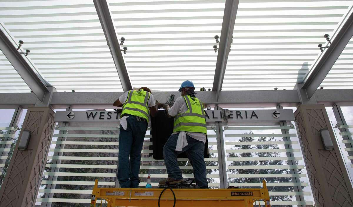 Electricians install an LED sign at a bus rapid transit platform at the intersection of Post Oak Blvd and Westheimer Road on July 1, 2020, in Uptown.