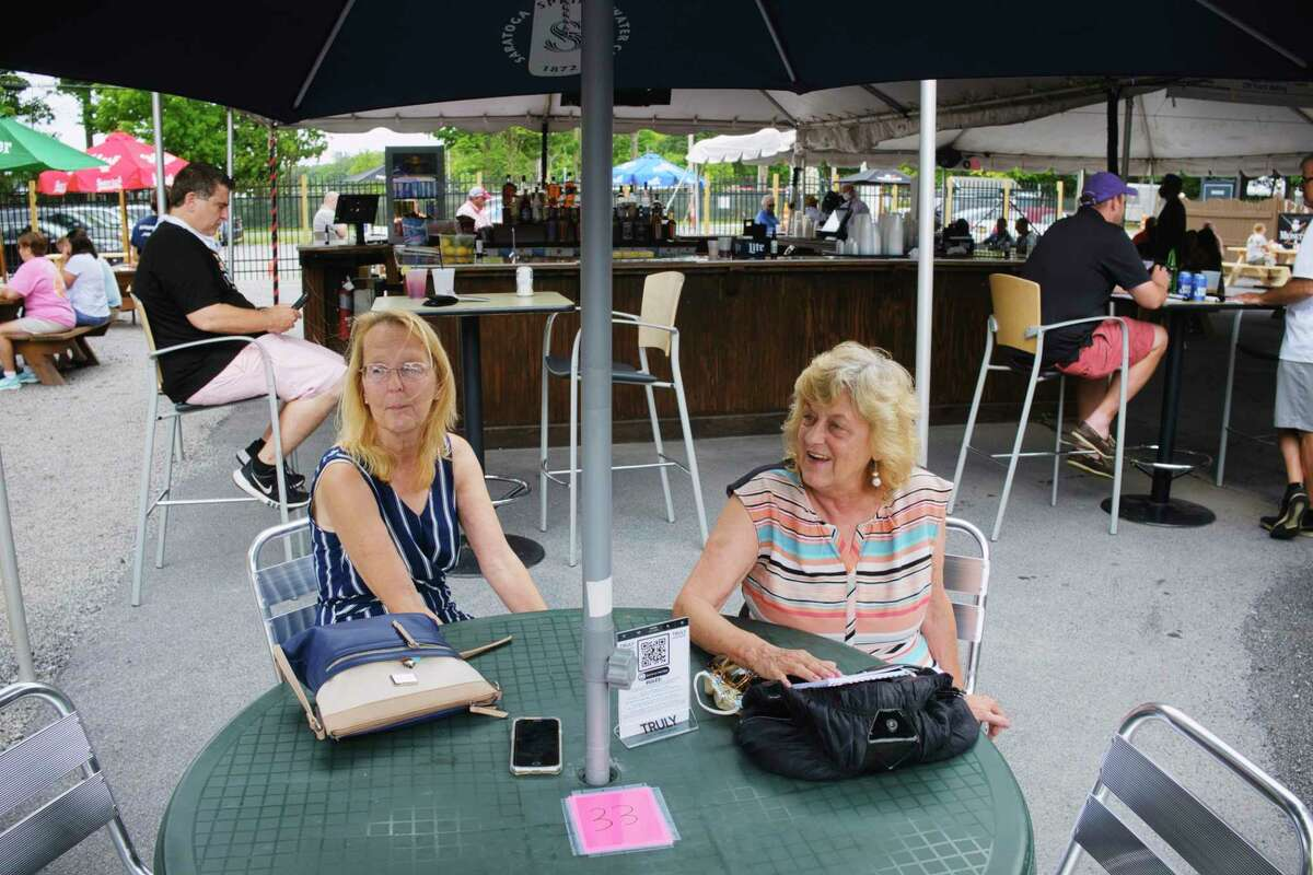 Friends, Carol Sutter, left, of Saratoga Springs, and Caroline Sgorrano of South Glens Falls, talk about Saratoga Race Course as they met up at the Horseshoe Inn Bar and Grill across from the track on Thursday, July 16, 2020, in Saratoga Springs, N.Y. For the past six years the two women have worked in guest services at the track. (Paul Buckowski/Times Union)