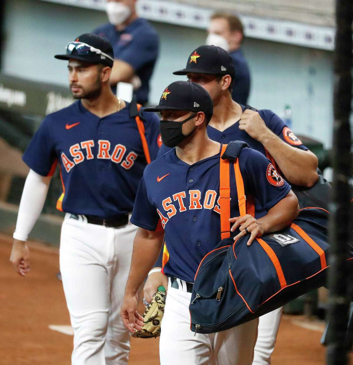 Houston Astros infielder Jack Mayfield wears a mask as he walks with others on the field before an intrasquad game during the Astros summer camp at Minute Maid Park, Thursday, July 16, 2020, in Houston.