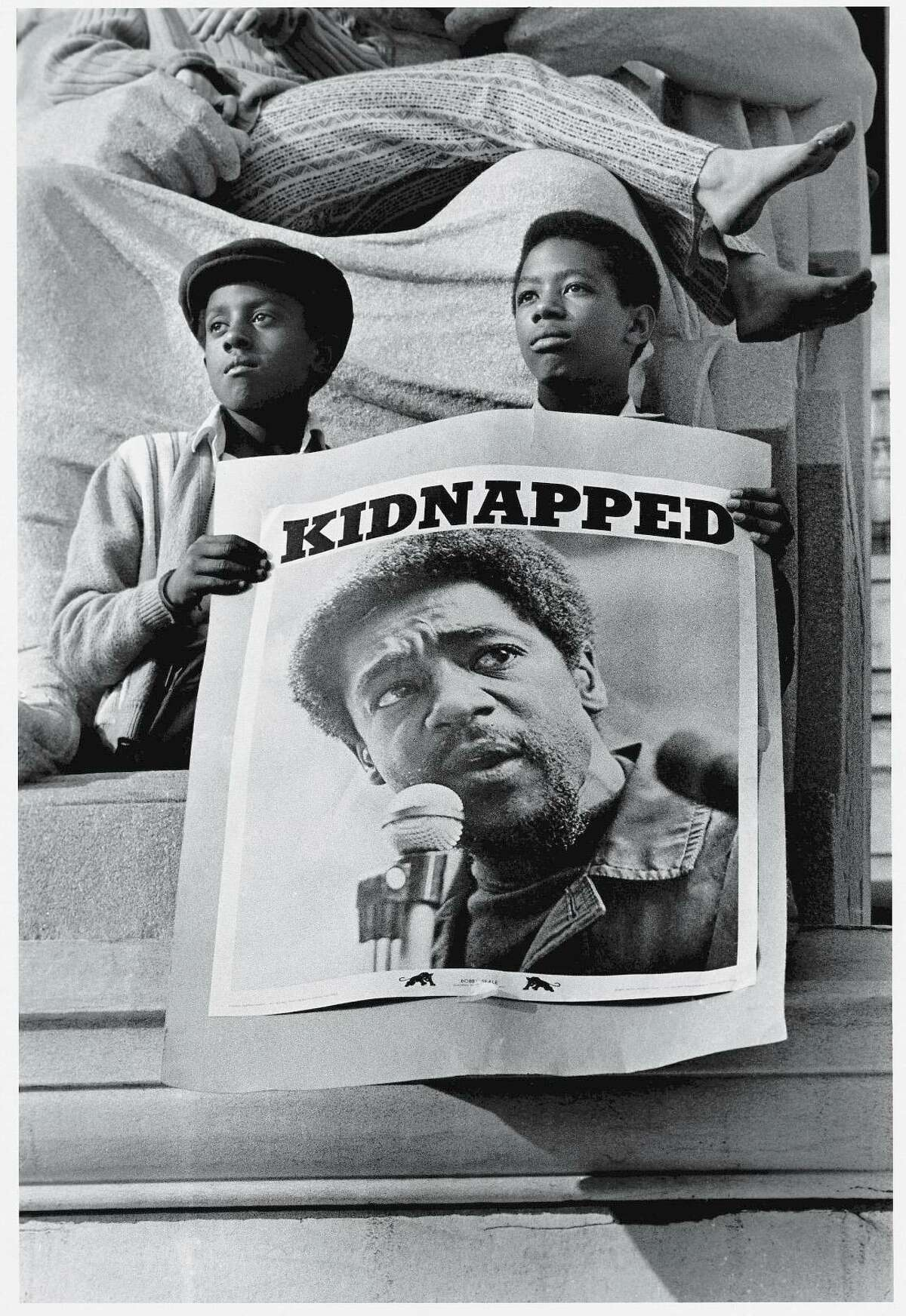 """At a rally in support of the Black Panther Party, two young men hold poster of Panther leader Bobby Seale under the heading """"Kidnapped,"""" in New Haven May 1, 1970. The poster refers to the trial of the New Haven Nine, of which Seale was one, which had just begun."""
