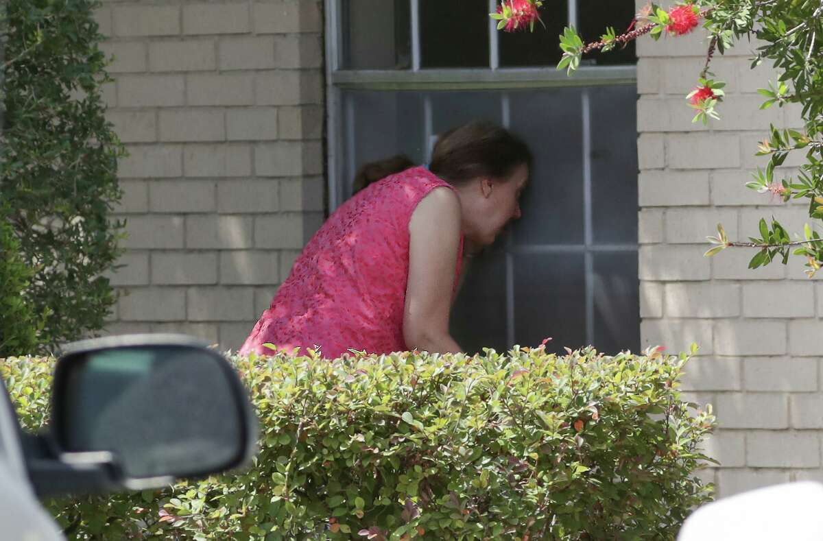 Charlyn Bhatti prays and leads Bible study with her 89-year-old mother, Roselyn Brown through a closed window on the side of Windsong Care Center Thursday, July 16, 2020, in Pearland.
