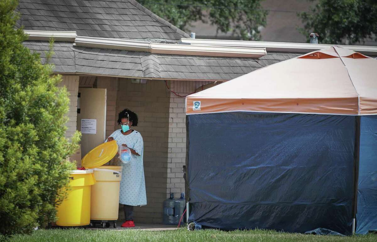 A woman disposes of a plastic bag in a yellow container in a hospital gown and gloves as PPE equipment at the Windsong Care Center Thursday, July 16, 2020, in Pearland.
