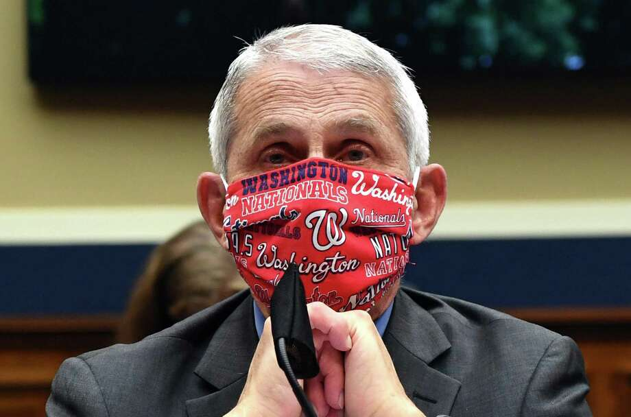 Dr. Anthony Fauci, director of the National Institute of Allergy and Infectious Diseases, wearing a Washington Nationals face mask, testifies at a hearing of the U.S. House Committee on Energy and Commerce on Capitol Hill on June 23. A recent Quinnipiac poll found that 65 percent of the public trust information Fauci gives on the coronavirus pandemic, while only 30 percent trust President Trump's information. Photo: Kevin Dietsch /Pool / TNS / Getty Images North America