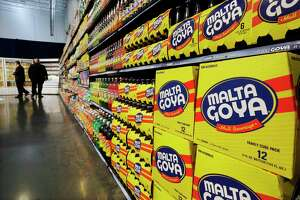 FILE - In this April 29, 2015, file photo, people walk past displays of Goya Foods products at the new corporate headquarters in Jersey City, N.J. Goya Foods is facing a a swift backlash after its CEO Robert Unanue praised President Donald Trump at White House event on Thursday, July 9, 2020. Almost immediately, Twitter exploded, with users both famous and not reminding Unanue of Trump's history of derogatory comments and harsh policies toward Hispanics, most notably, the administration's policy of separating immigrant families at the U.S.-Mexico border. (AP Photo/Mel Evans, File)
