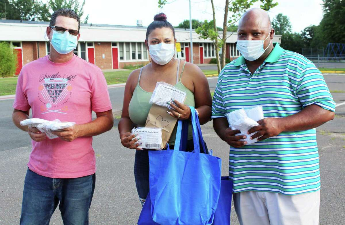 From left, members of the Middlesex County Community of Color recently distributed 2,000 face masks, bottles of sanitizer, and other items to help prevent the spread of the coronavirus at Stonybrook Commons and Rose Circle in Middletown. At right is Middletown Police Capt. Gary Wallace; his fiancee Karina Marrinan at center, and Sean Mulligan of EB Manufacturing, left.