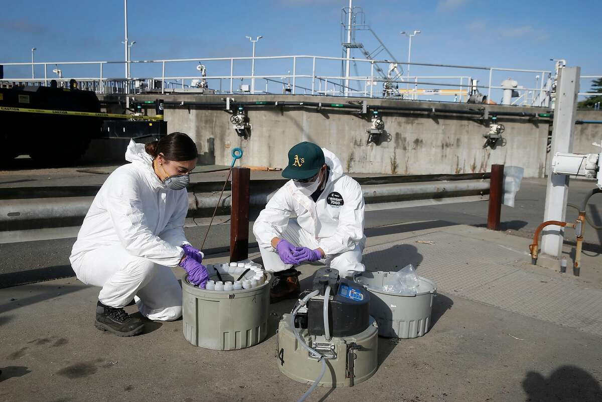 Gabriela Esparza and Zach Wu, wastewater control inspectors with EBMUD, cap 24 separate bottles while retrieving collection equipment and the samples in Oakland, Calif. on Tuesday, July 14, 2020. The samples are sent to a number of labs to analyze for any detection of the COVID-19 coronavirus in the sewage system.