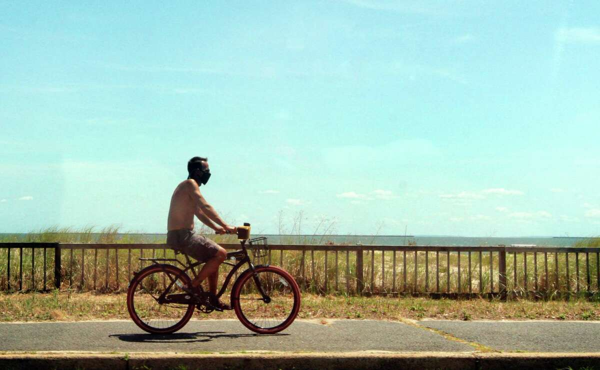 A man enjoys the warm summer weather with a bike ride along Beach Street in West Haven, Conn.