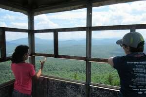 Outdoor writer Gillian Scott and her daughter in the cab of the fire tower on Stillwater Mountain in Old Forge several weeks ago. (Herb Terns / Times Union)