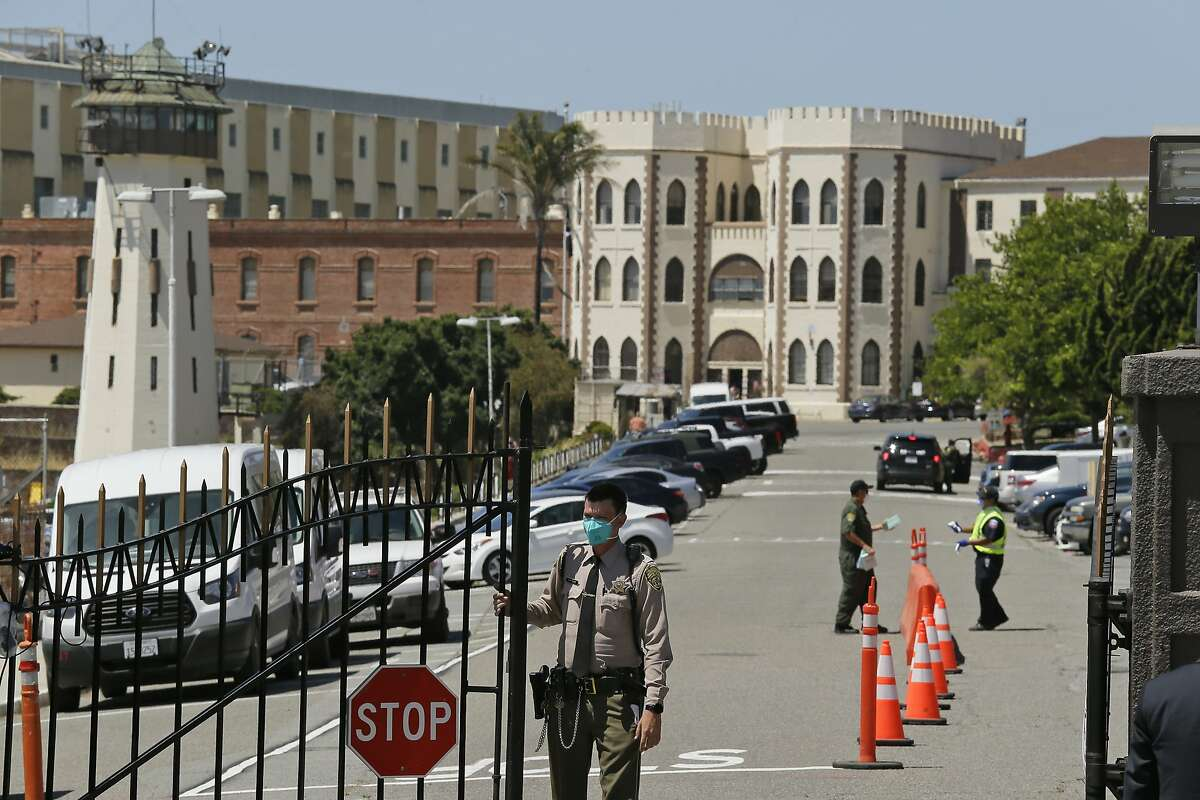 In this July 9, 2020, file photo, a correctional officer closes the main gate at San Quentin State Prison in San Quentin, Calif. The death of a 66-year-old man found in his San Quentin cell early Wednesday morning is being investigated as a homicide, while his 28-year-old cellmate has been named as the suspect, prison officials said Wednesday.